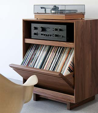 The AERO Entertainment Cabinet is handcrafted with North American hardwoods. Includes a swivel-style LP storage bin. Features room for Hi-Fi audio equipment. Is sitting in a living room setting.